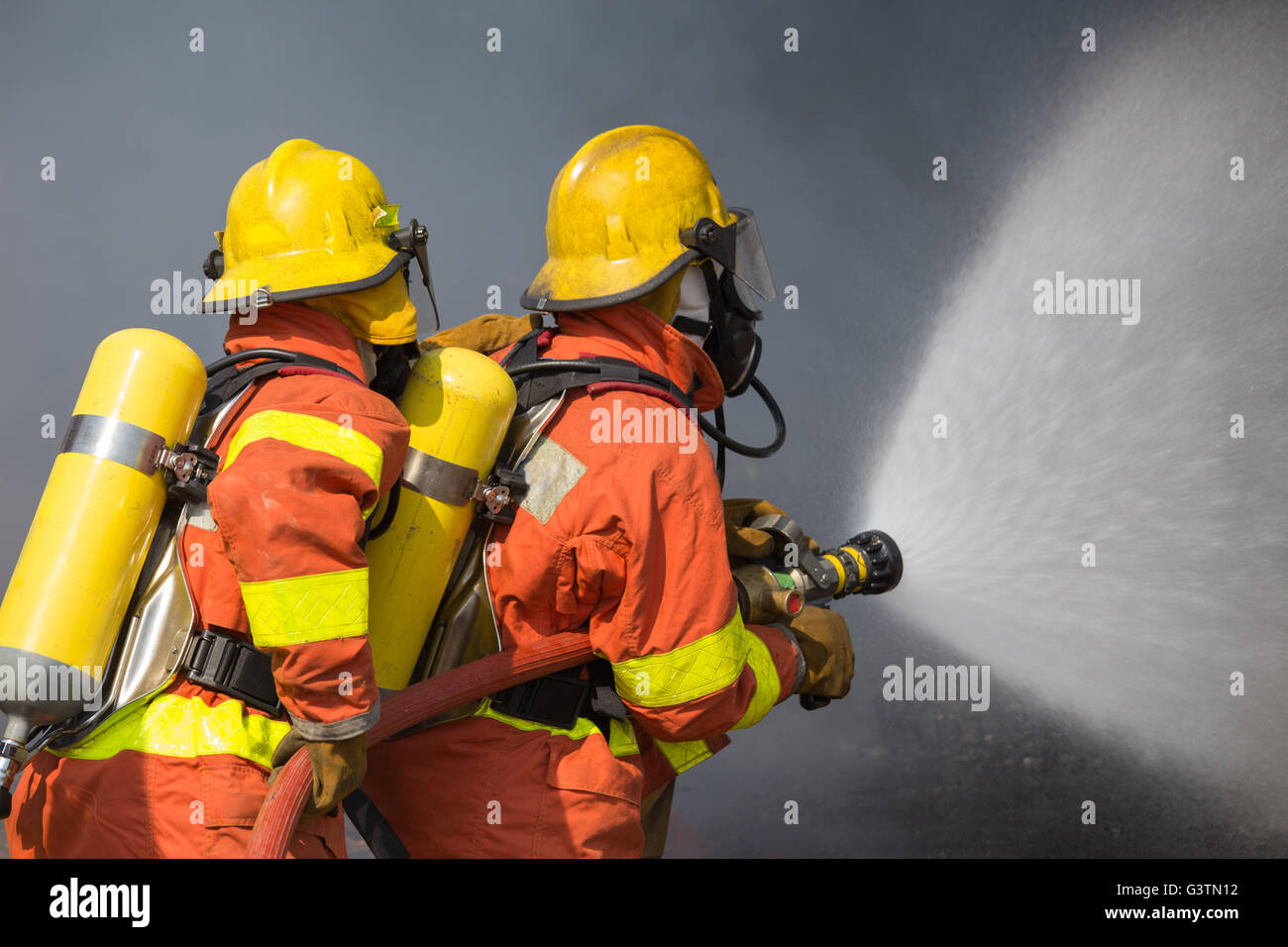 2 firefighters spraying water in fire fighting with dark smoke background - Stock Image