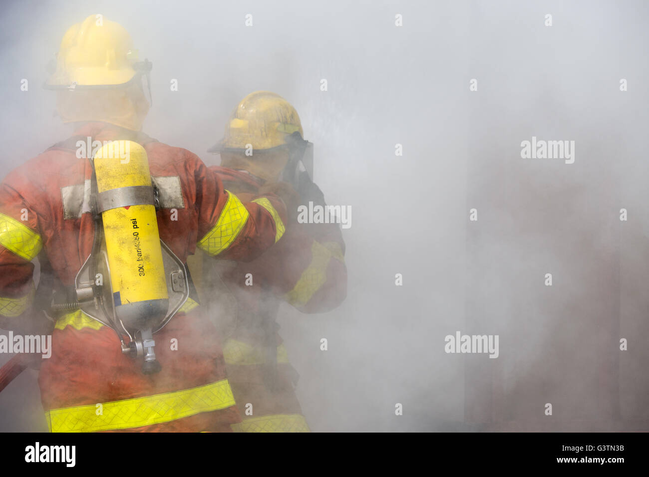 2 firemen in operation surround with smoke - Stock Image