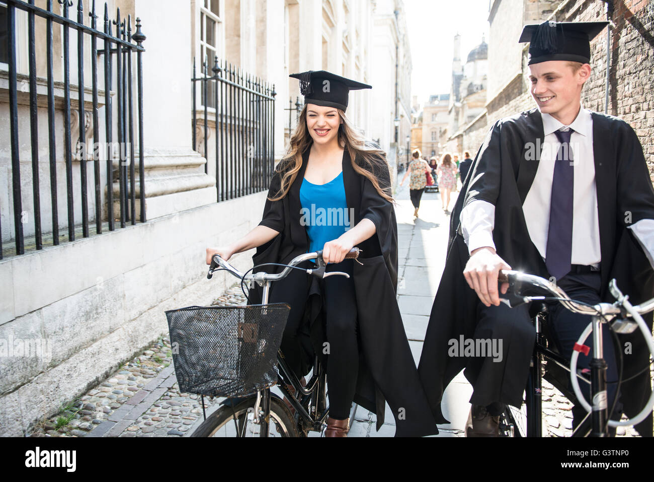 Two young students in graduation gowns cycling through the grounds of Cambridge University. - Stock Image
