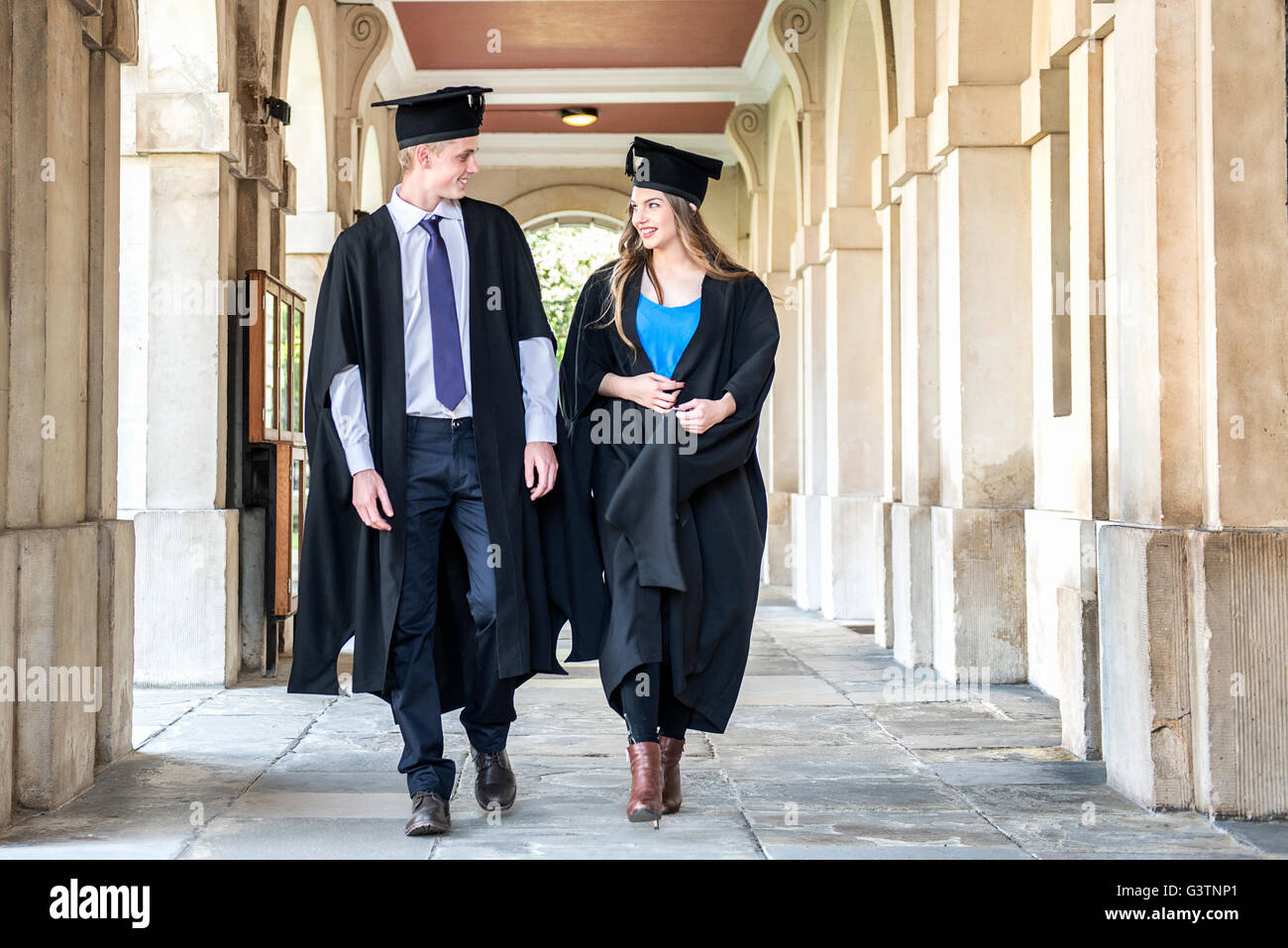 Two students in graduation gowns walking outside a building at Cambridge University. - Stock Image