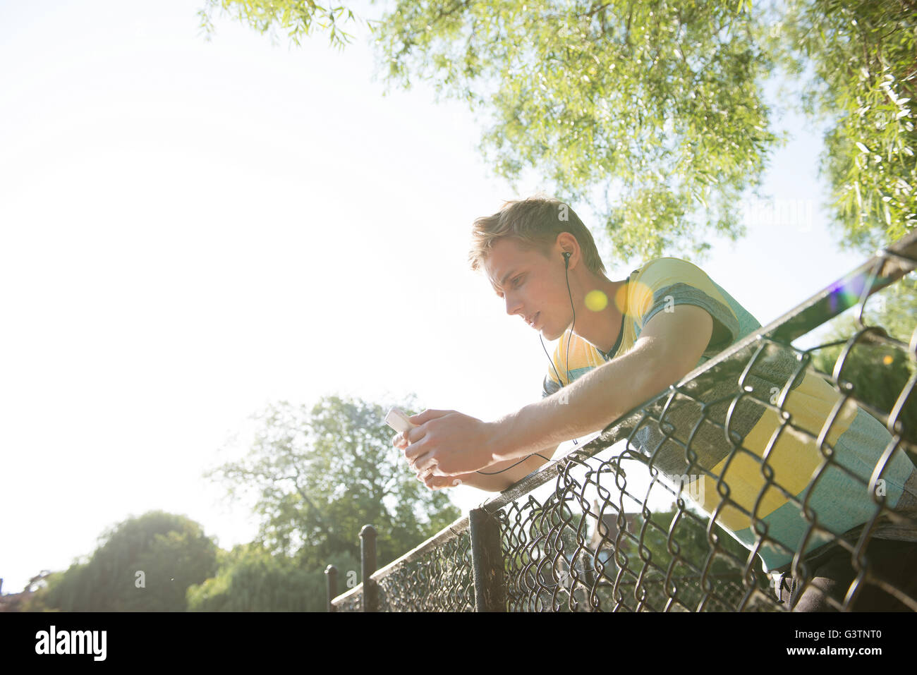 A young man leans on a railing listening to music through headphones. - Stock Image