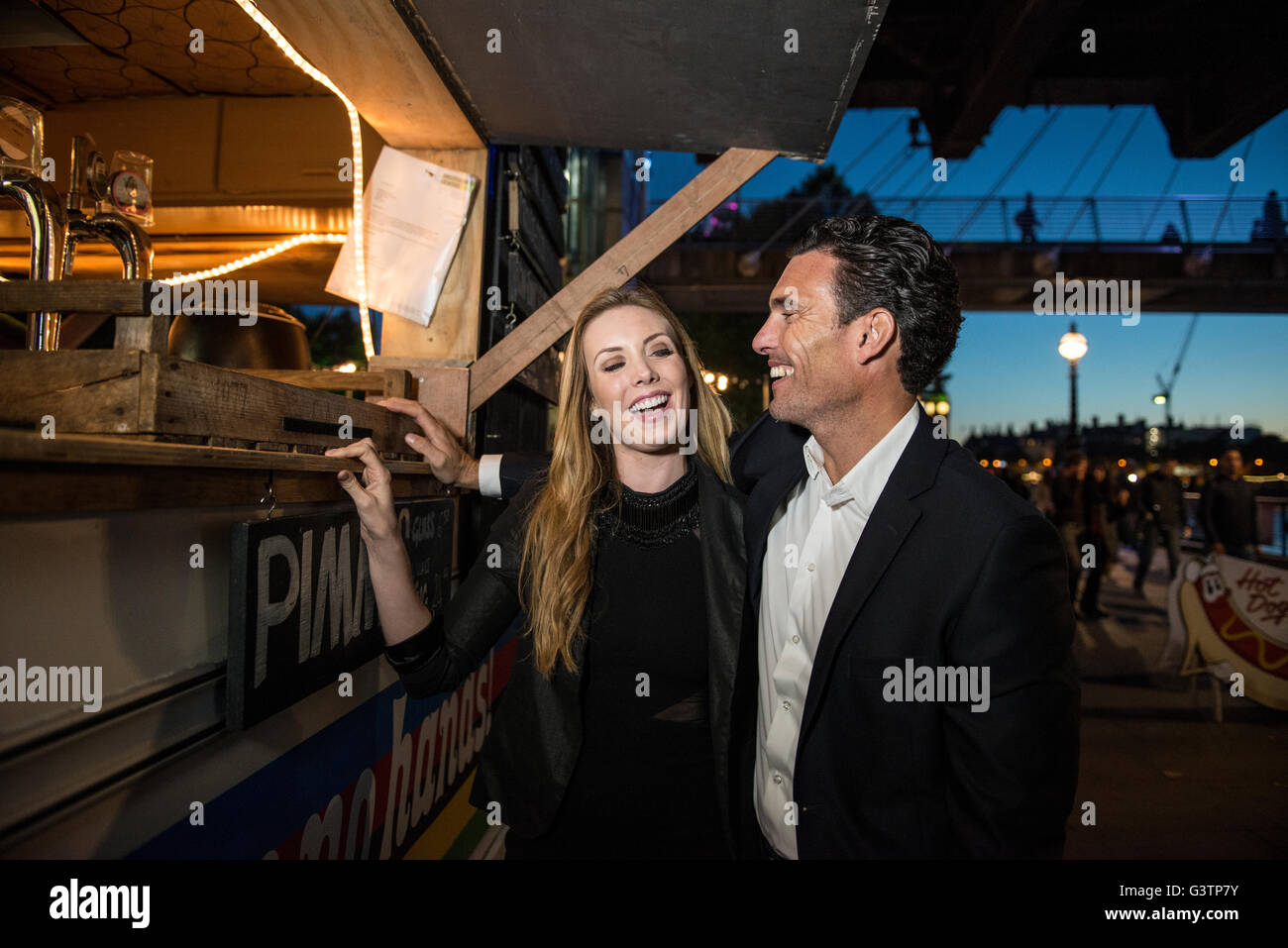 A smartly dressed couple buying drinks from a kiosk on the South Bank in London. - Stock Image