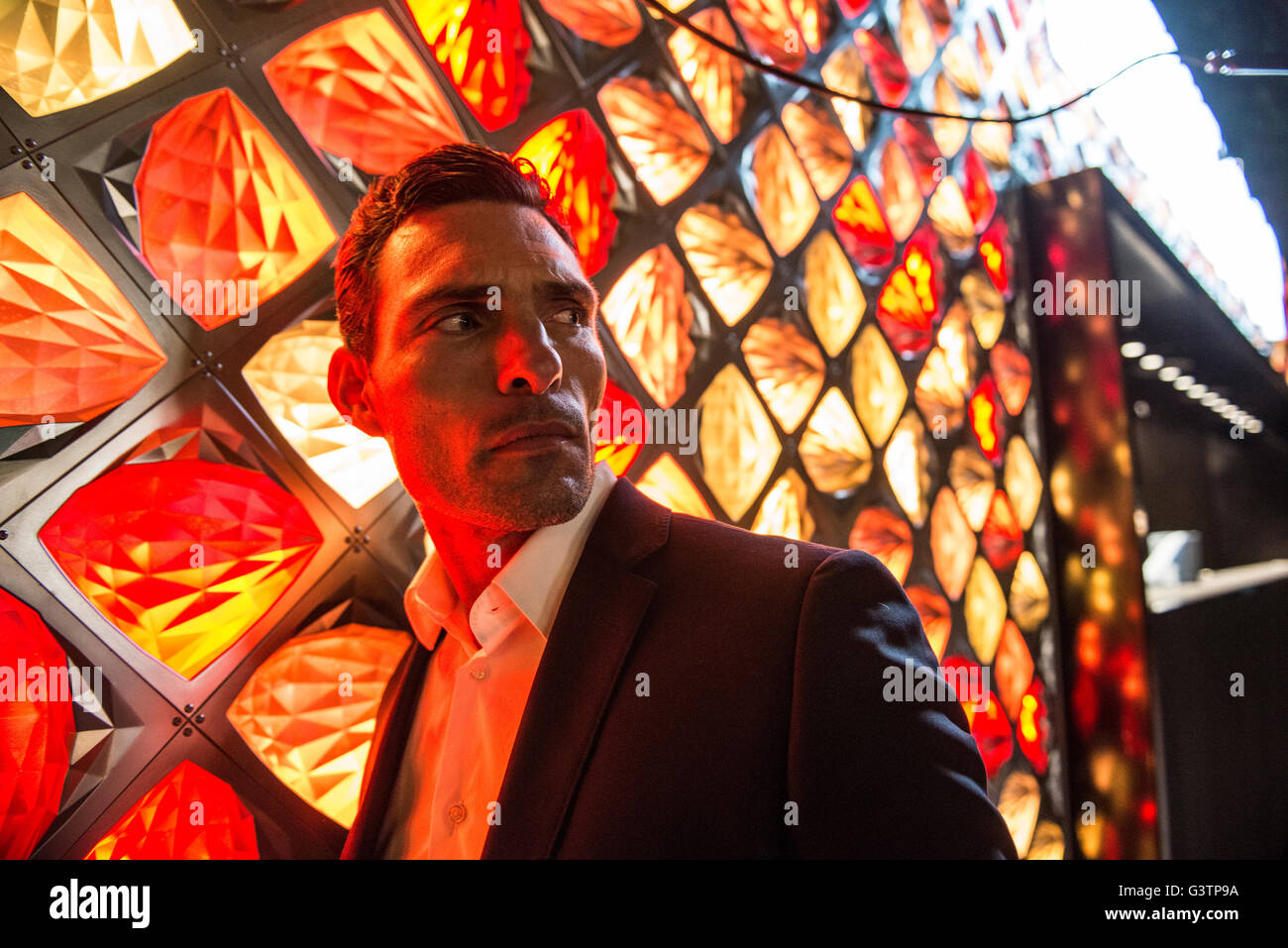 A smartly dressed man bathed in red light in front of a light fixture on the South Bank in London. - Stock Image