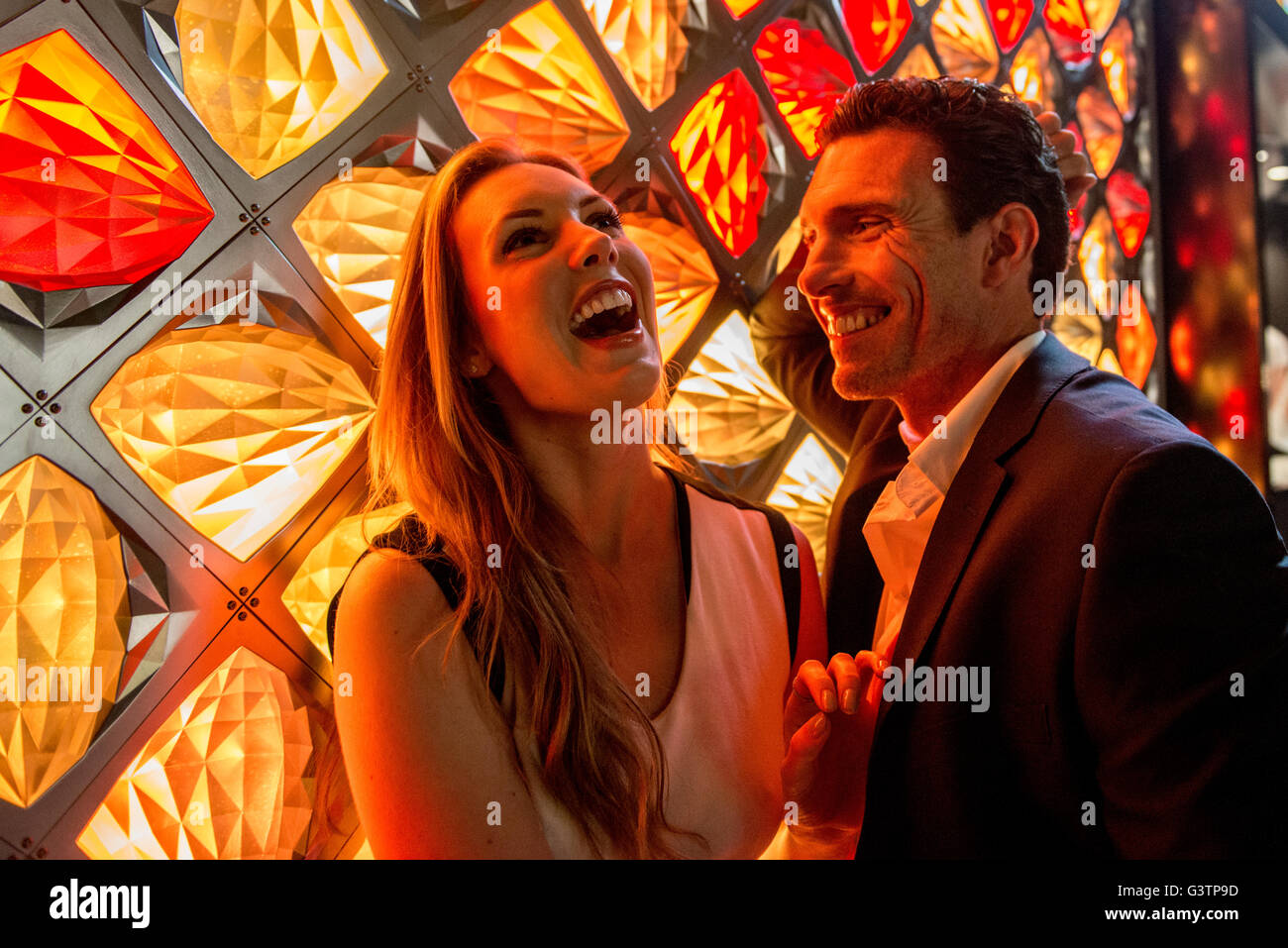 A smartly dressed couple laughing in front of a light fixture on the South Bank in London. - Stock Image