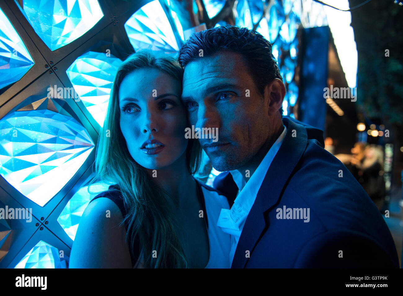 A smartly dressed couple bathed in blue light in front of a light fixture on the South Bank in London. - Stock Image