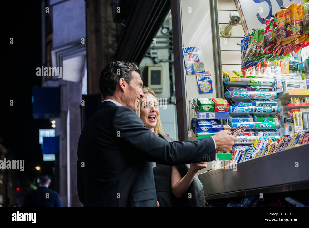 A smartly dressed couple buying confectionary from a kiosk on Oxford Street in London. - Stock Image