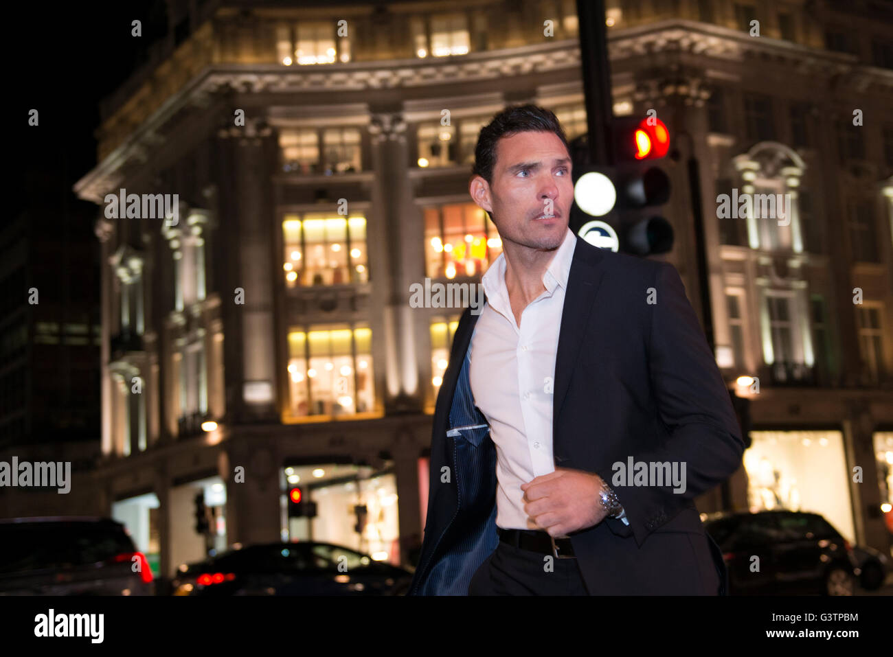 A smartly dressed man walking at Piccadilly Circus in London. - Stock Image
