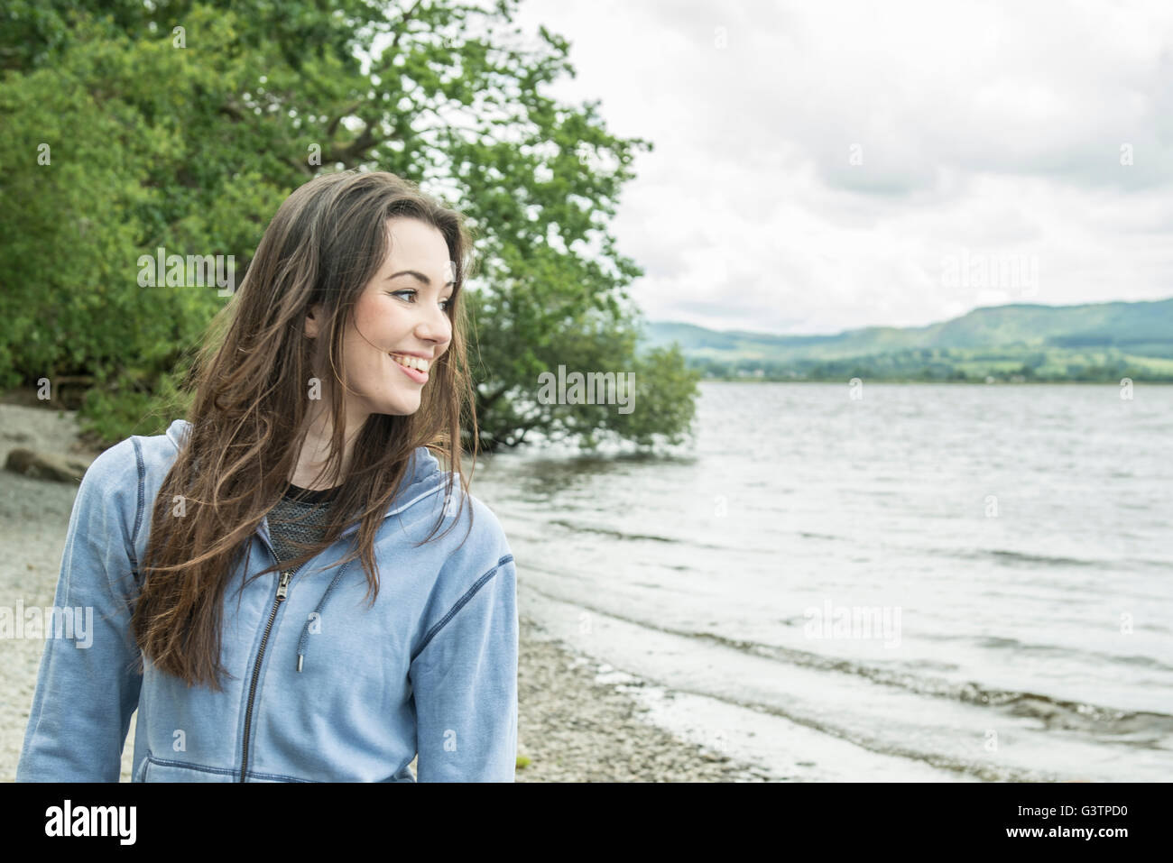 A girl standing smiling on the shore beside Bala Lake in Wales. - Stock Image
