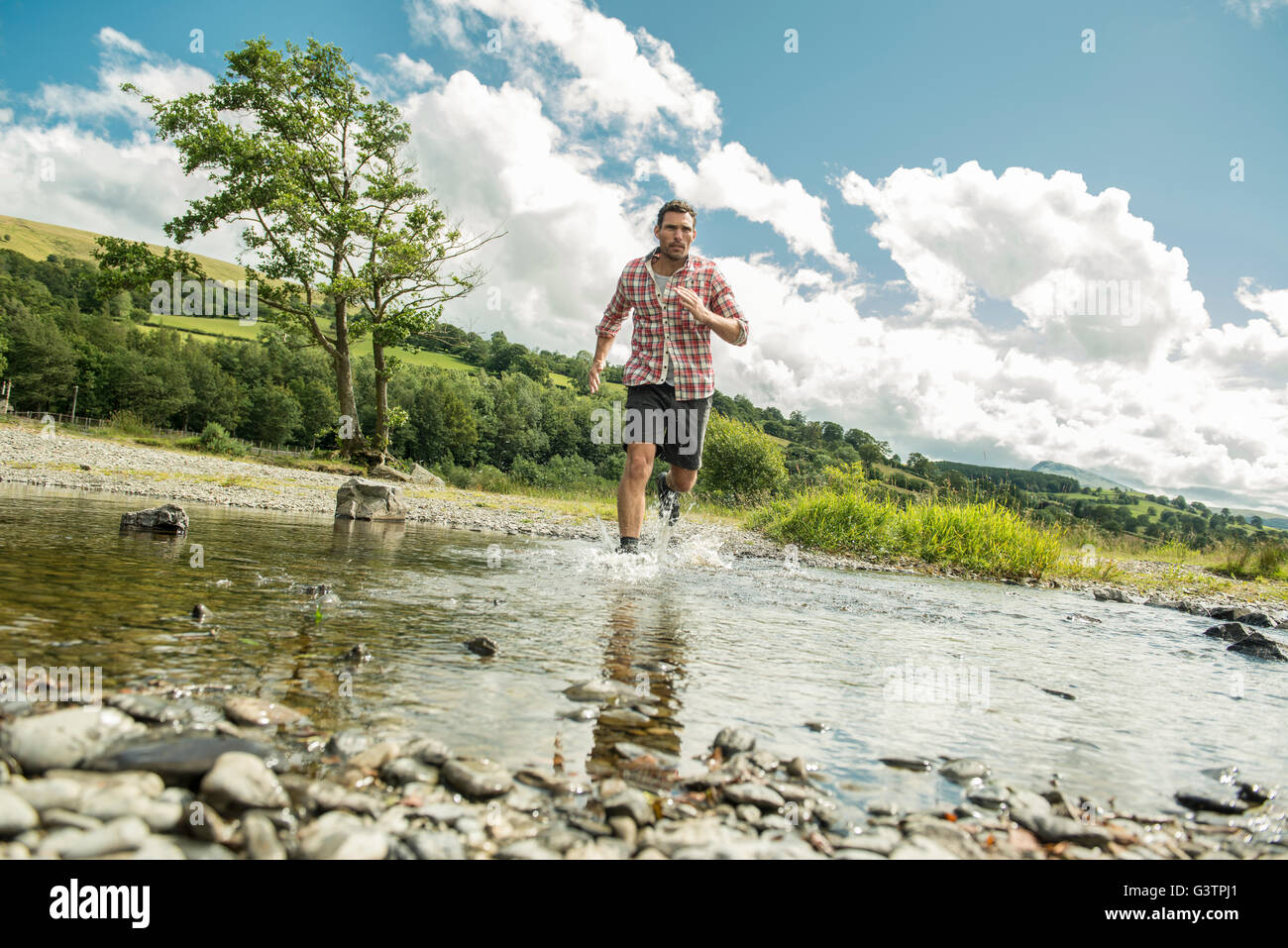A man in a red check shirt striding across a shallow river near Bala Lake in Wales. - Stock Image