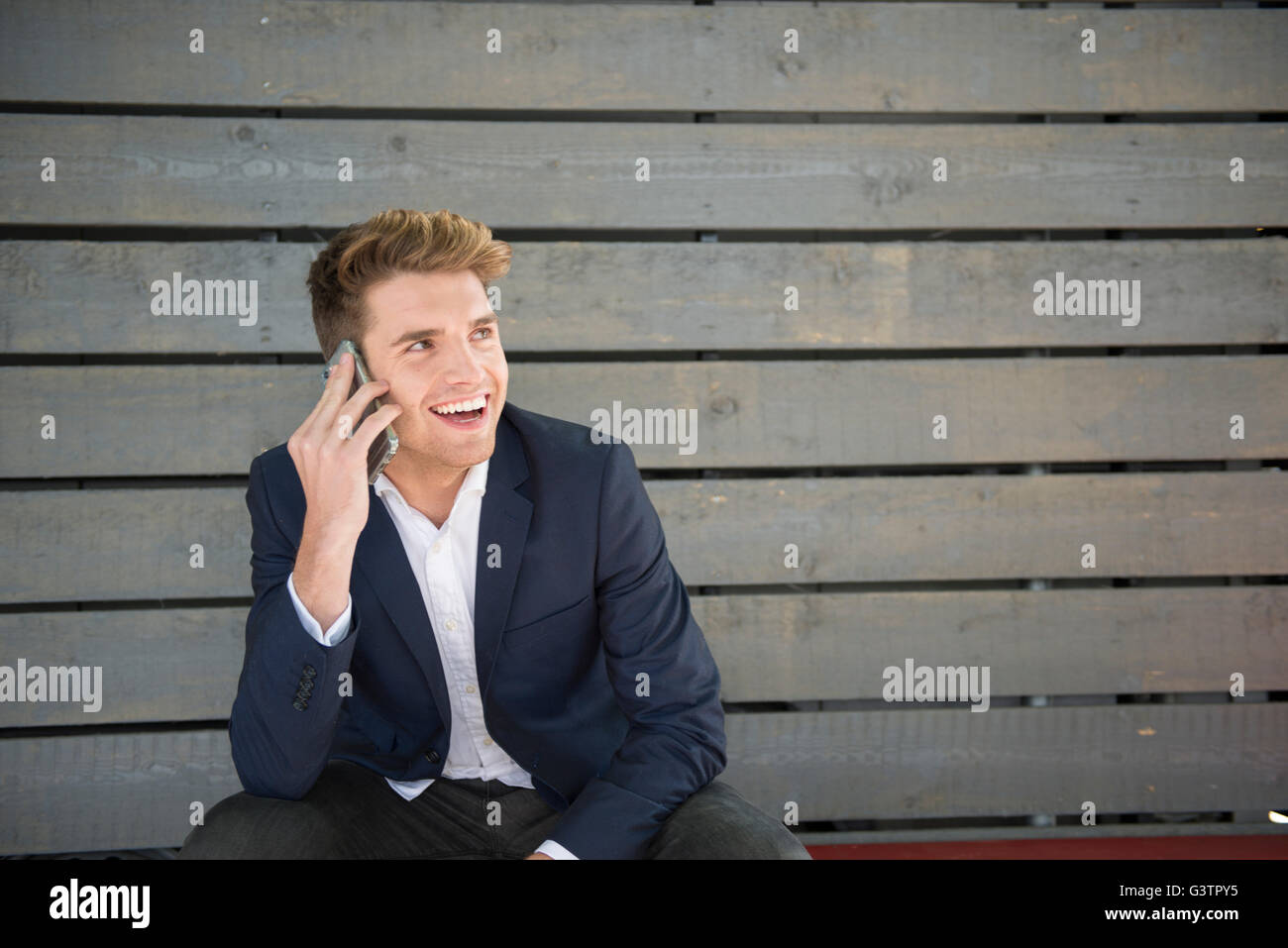 A young man sitting on a bench making a phone call on the South Bank in London. - Stock Image