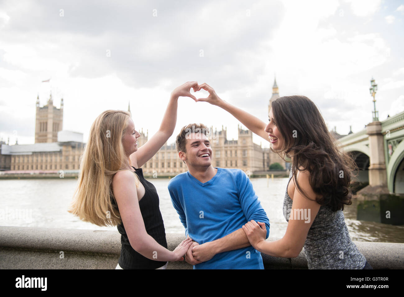 Three friends make a heart shape with their hands with the Houses of Parliament in the background. - Stock Image