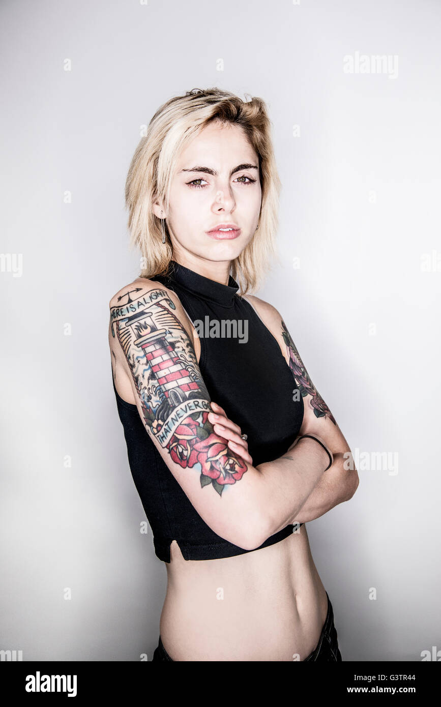 A young tattooed woman posing in a studio looking wistful. - Stock Image