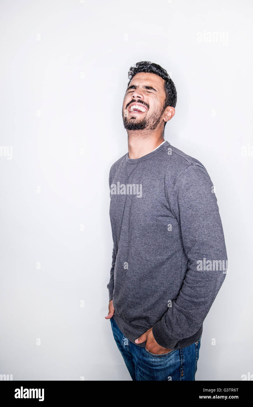 A young man posing in a studio laughing. - Stock Image