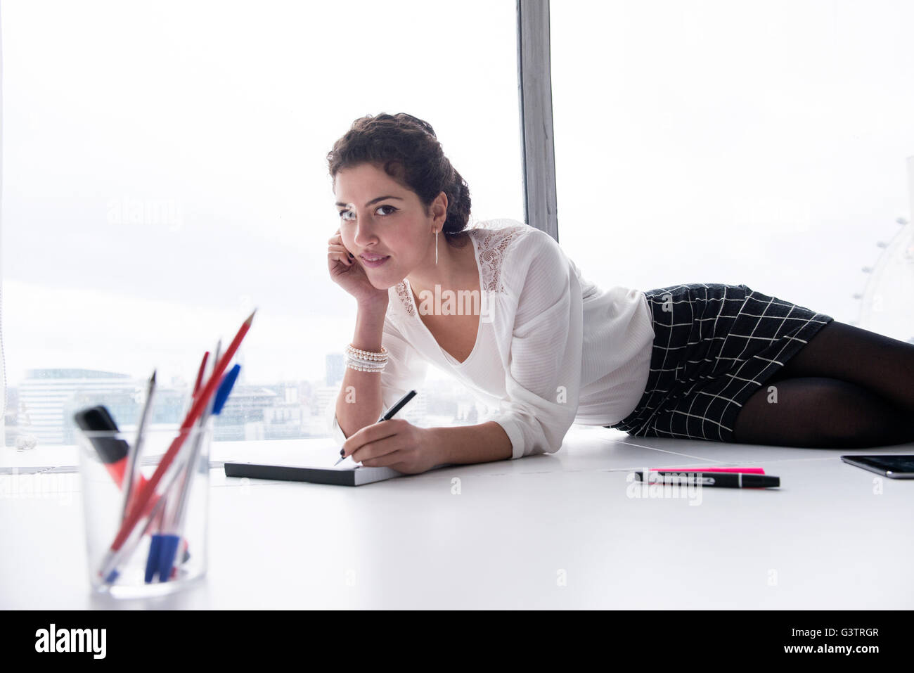 A professional woman making notes on a pad in a high rise office environment. - Stock Image