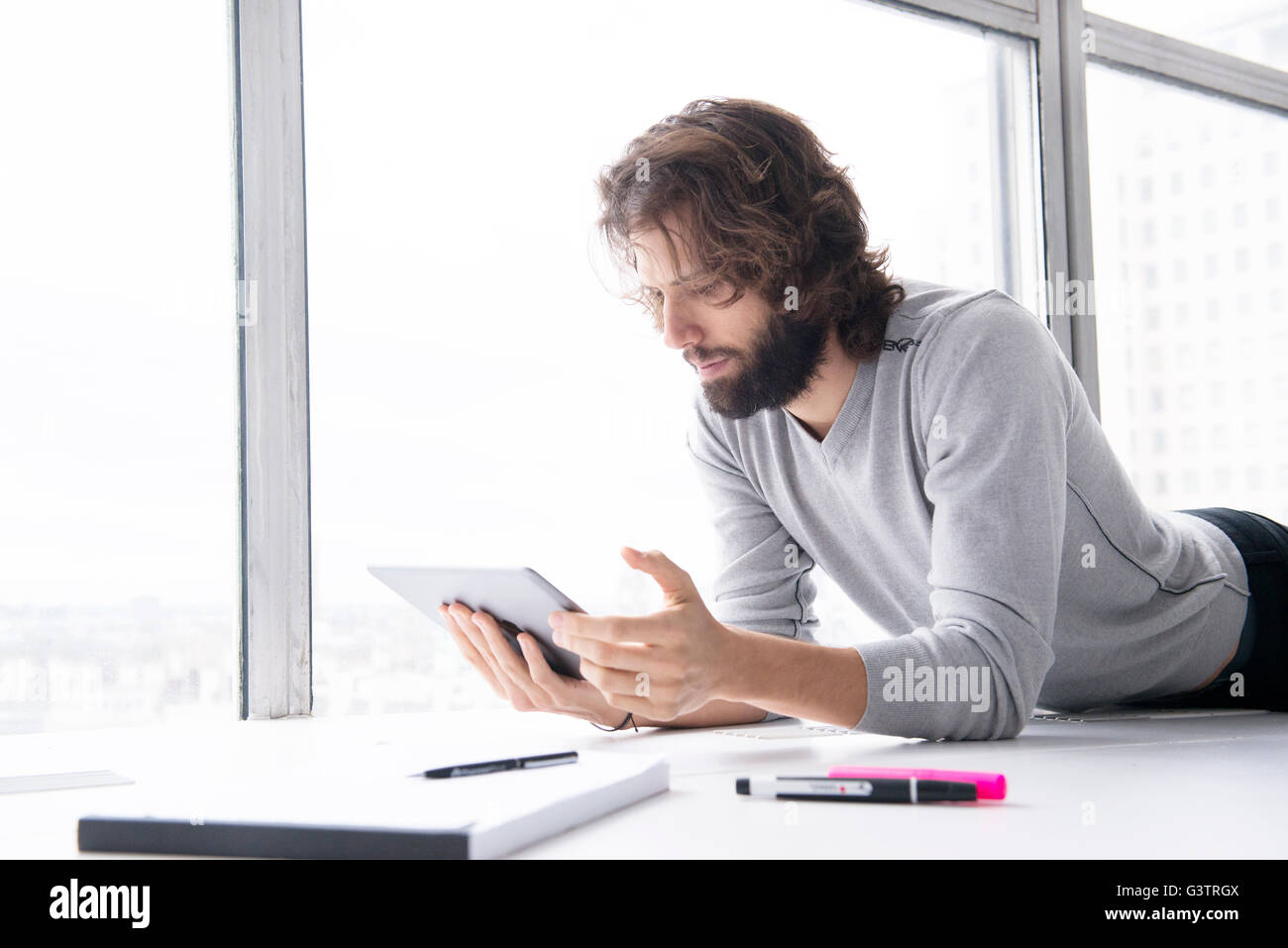 A professional man making notes on a tablet computer in a high rise office environment. - Stock Image