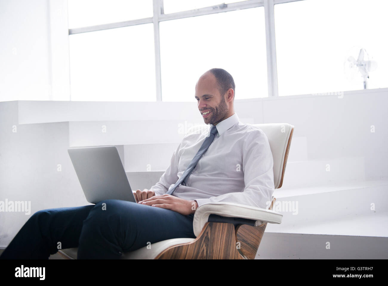 A professional man sitting making notes on a laptop in a business environment. - Stock Image