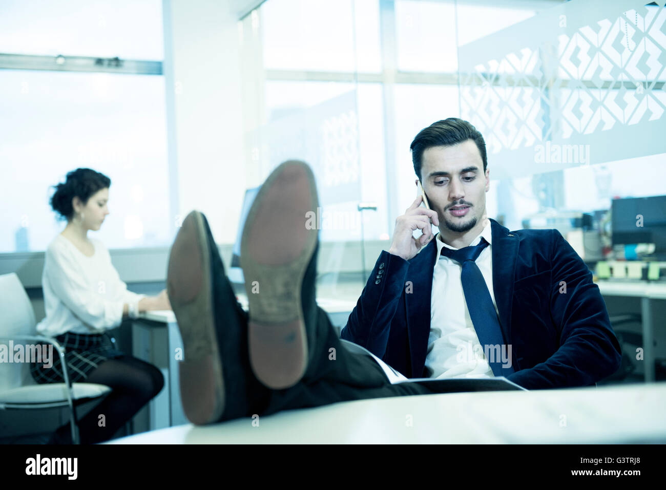 A professional man making a phone call in an office environment. - Stock Image