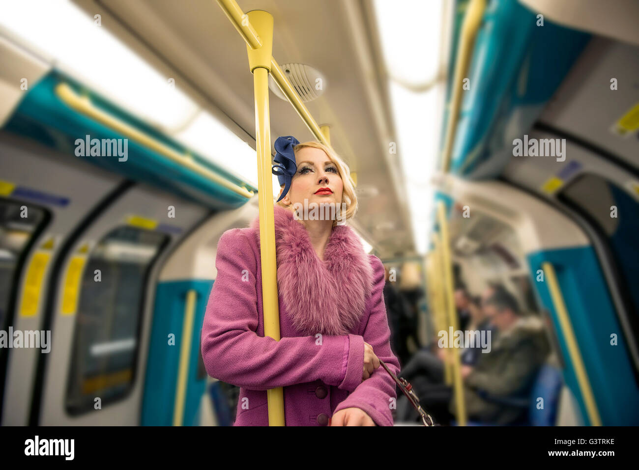 A stylish young woman dressed in 1930s style clothing travelling on a tube train. - Stock Image