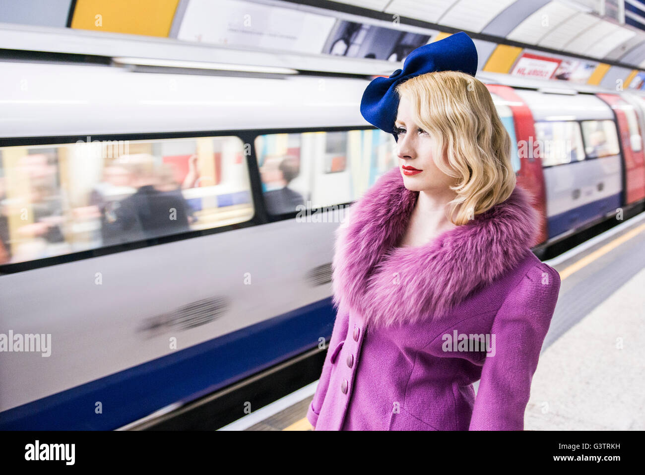 A stylish young woman dressed in 1930s style clothing standing on a tube platform. - Stock Image