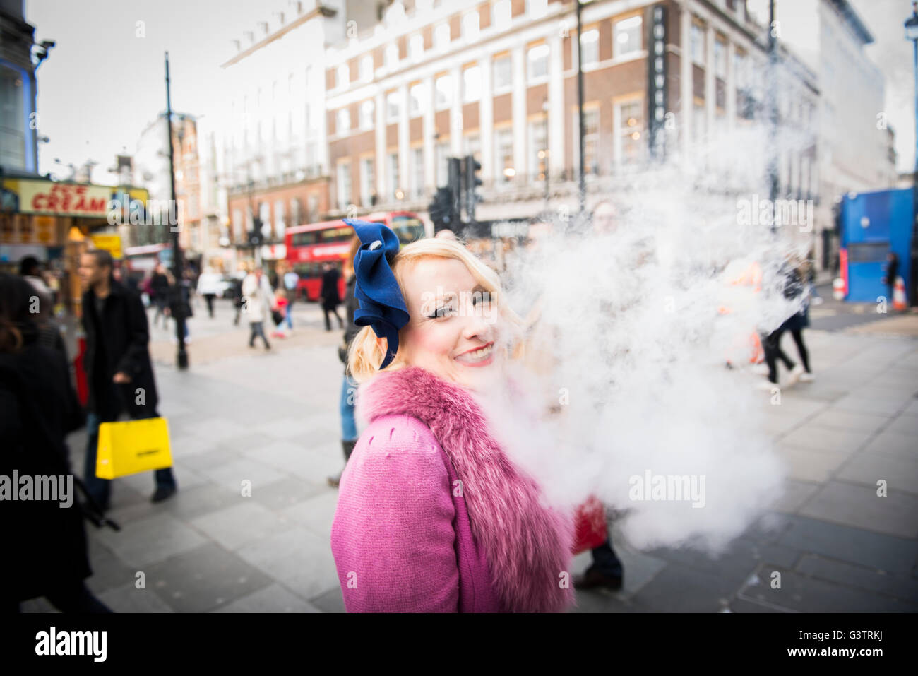A stylish young woman dressed in 1930s style clothing smoking a cigarette on a street in London. - Stock Image