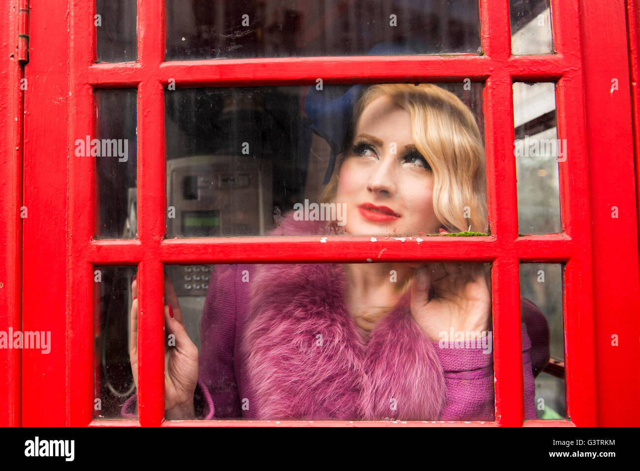A stylish young woman dressed in 1930s style clothing standing in a traditional telephone kiosk on a London street. - Stock Image