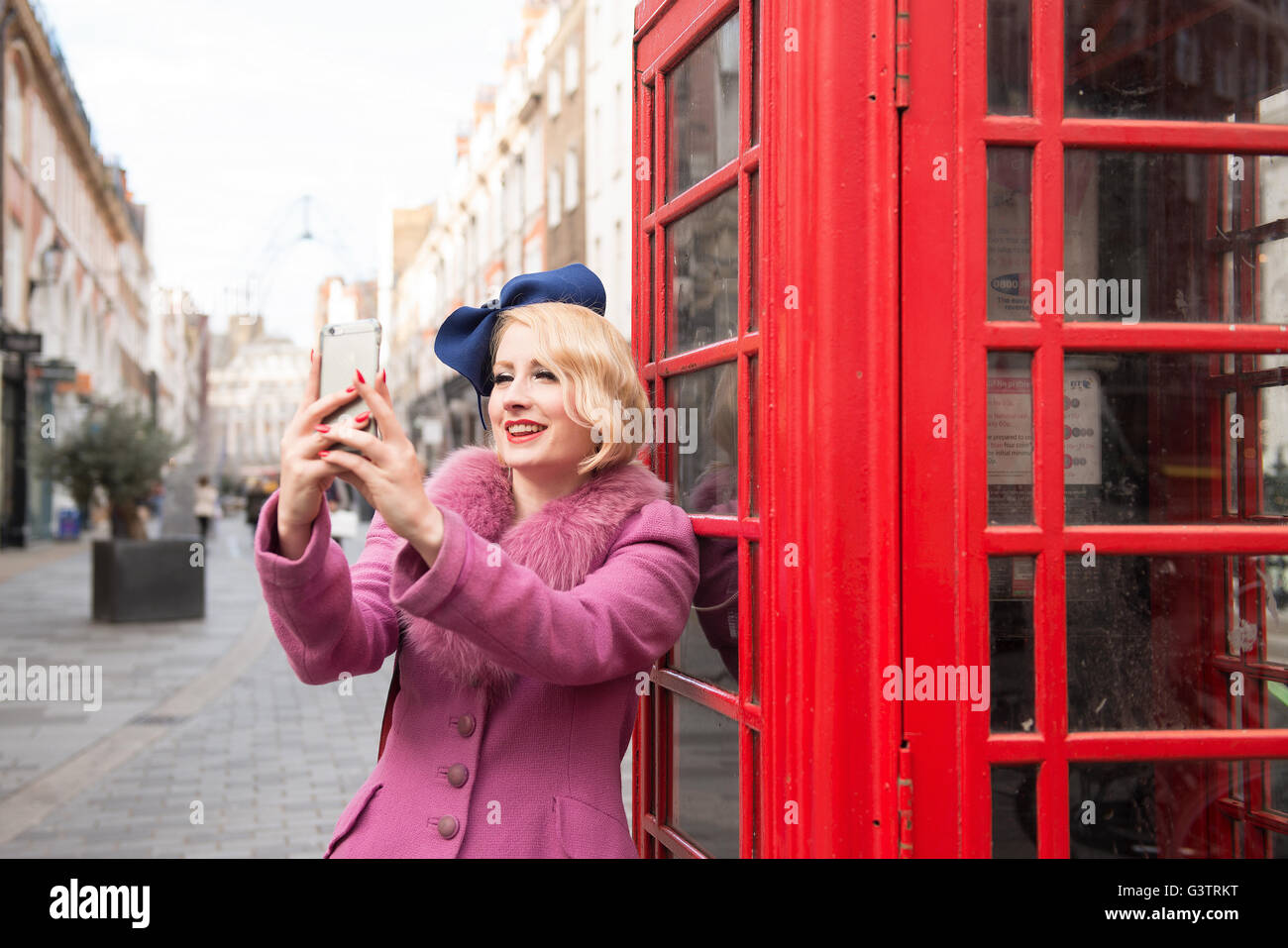A stylish young woman dressed in 1930s style clothing taking a selfie outside a traditional telephone kiosk on a - Stock Image