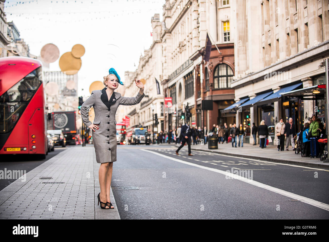 A stylish young woman dressed in 1930s style clothing hailing a taxi on Regent Street in London. - Stock Image