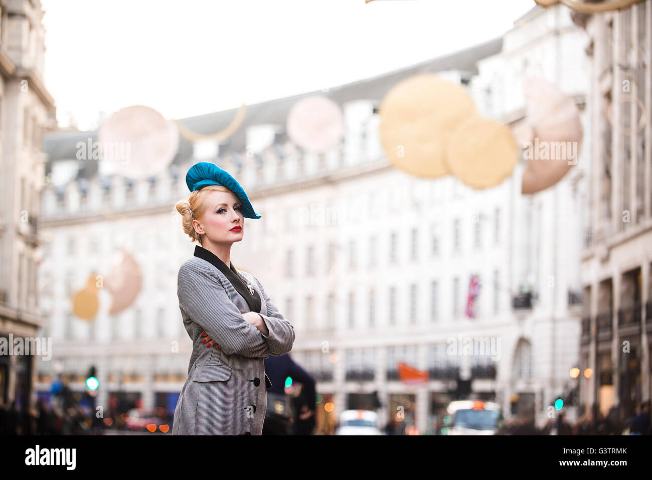 A stylish young woman dressed in 1930s style clothing waiting for a taxi on Regent Street in London. - Stock Image