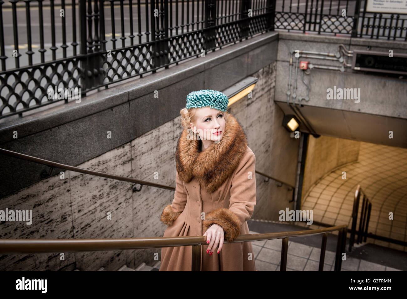 A stylish young woman dressed in 1930s style clothing walking up stairs from Piccadilly Circus tube station. - Stock Image