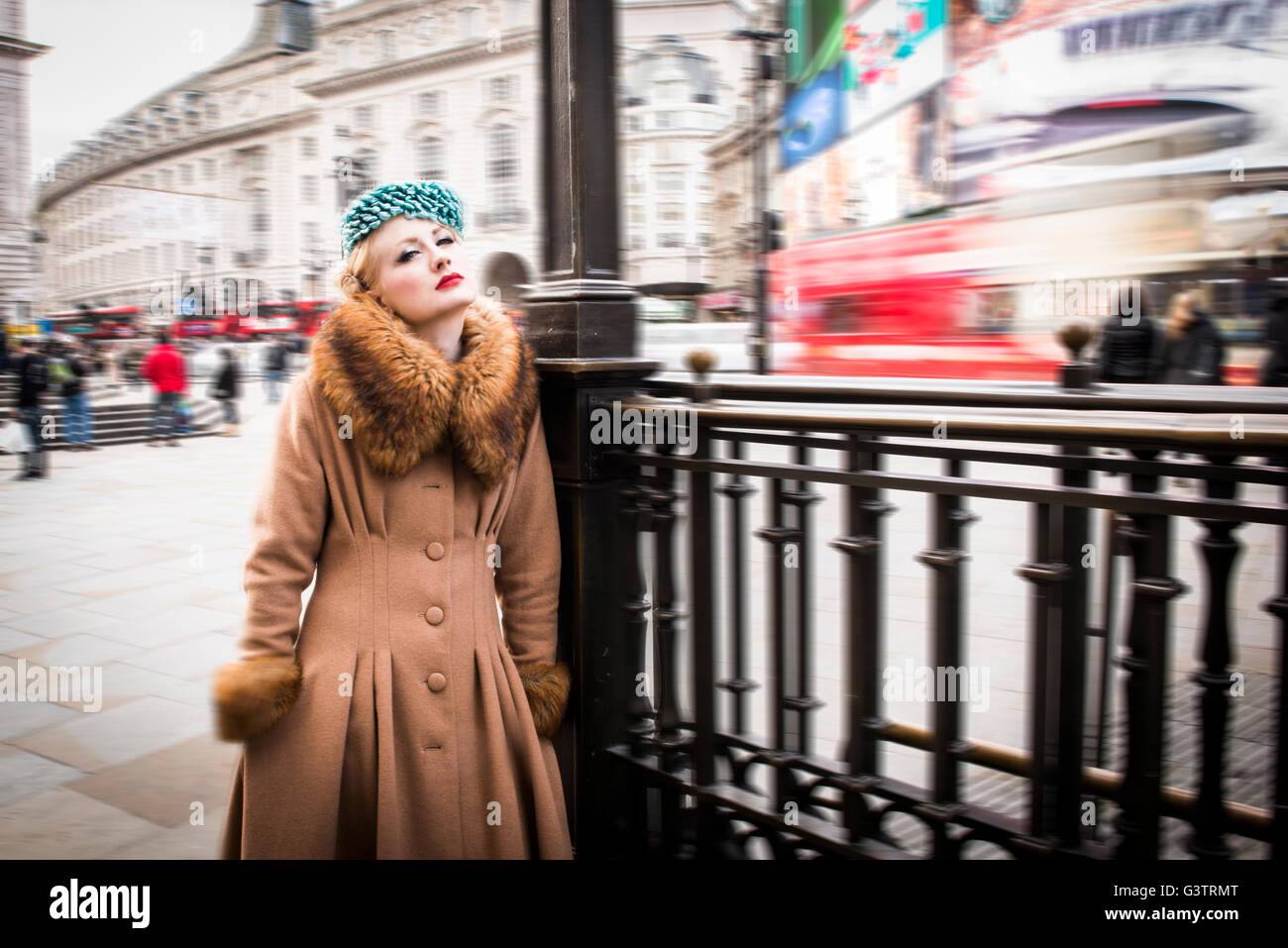A stylish young woman dressed in 1930s style clothing standing by railings at the entrance to Piccadilly Circus - Stock Image