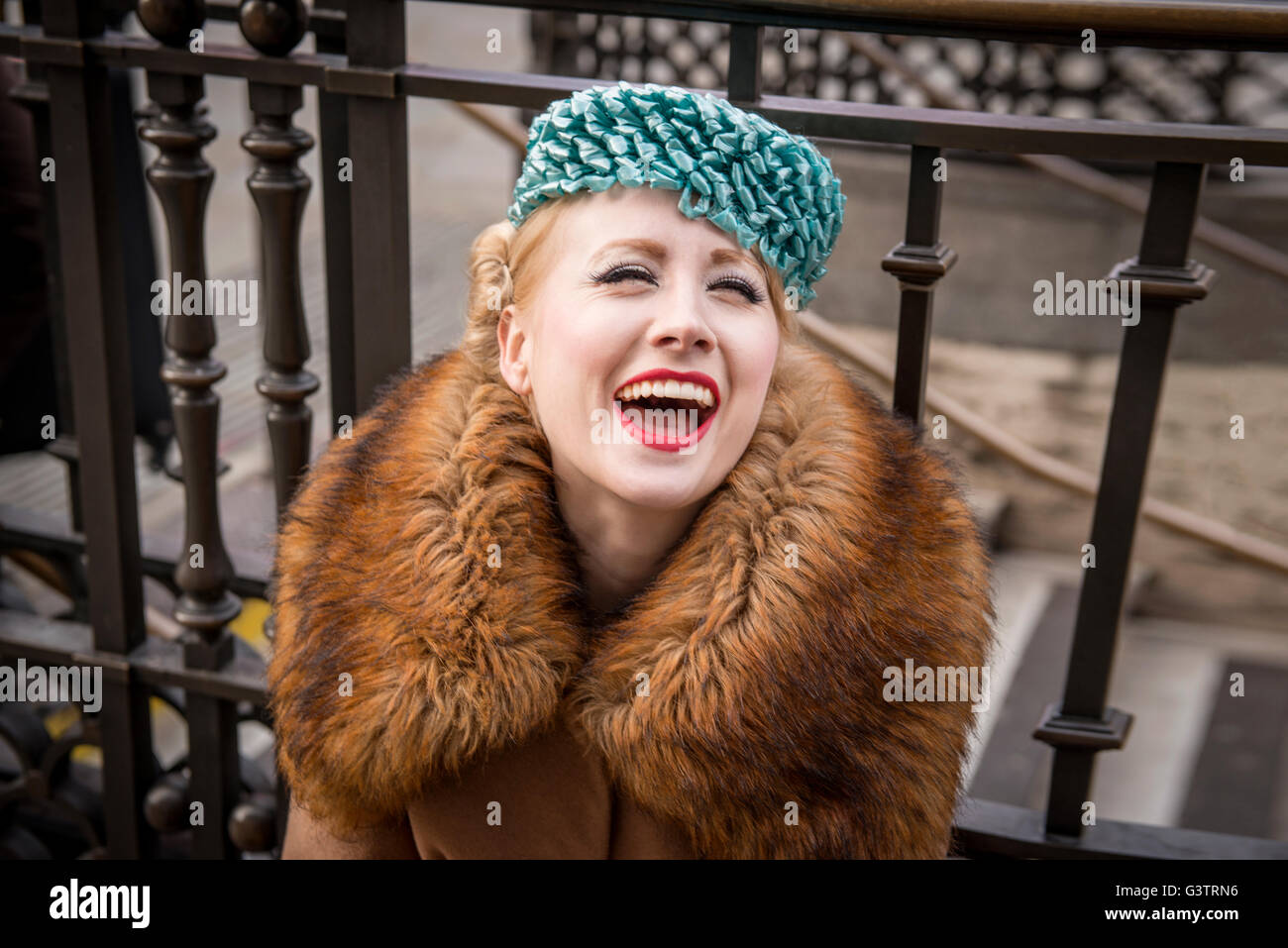 A stylish young woman dressed in 1930s style clothing sitting laughing by railings at the entrance to Piccadilly - Stock Image