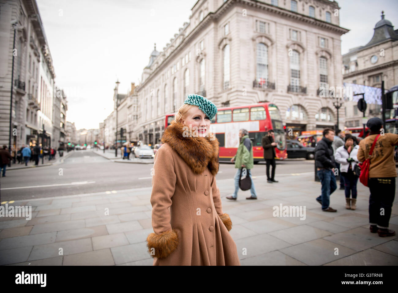 A stylish young woman dressed in 1930s style clothing walking about at Piccadilly Circus. - Stock Image