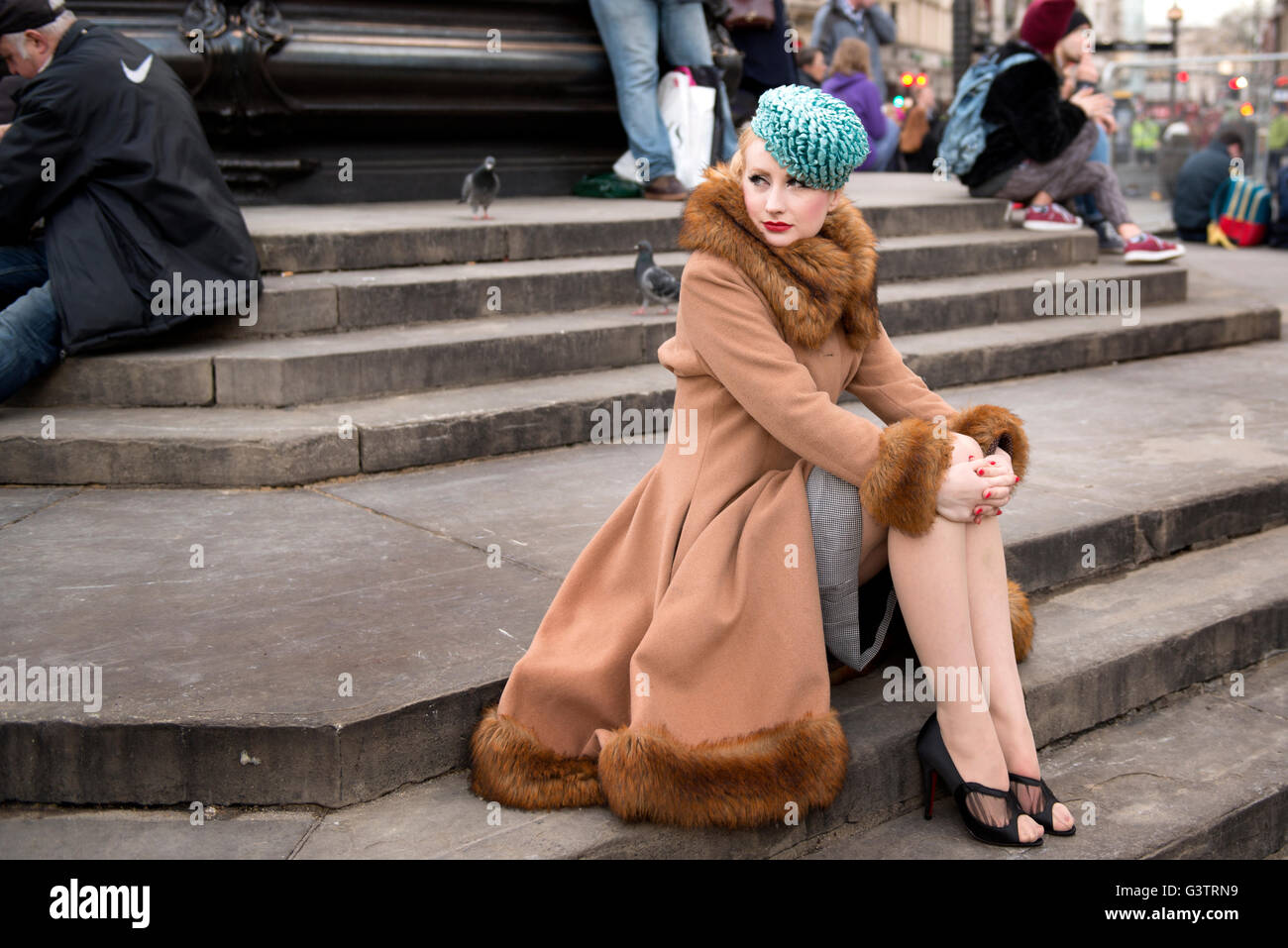 A stylish young woman dressed in 1930s style clothing sitting by the statue of Eros at Piccadilly Circus. - Stock Image