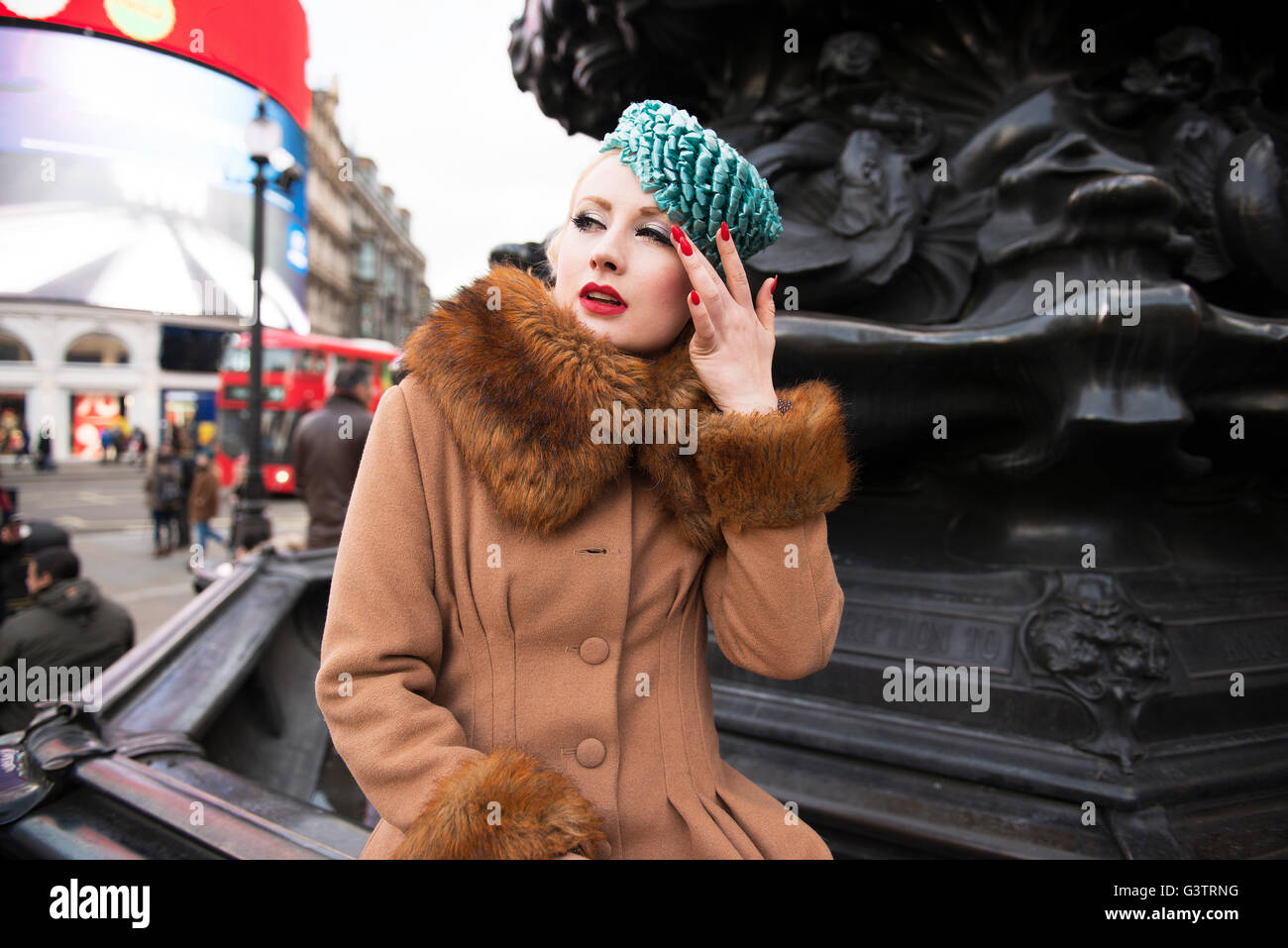 A stylish young woman dressed in 1930s style clothing standing by the statue of Eros at Piccadilly Circus. - Stock Image