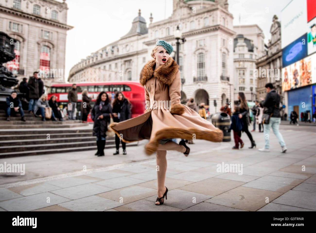 A stylish young woman dressed in 1930s style clothing twirling around by the statue of Eros at Piccadilly Circus. - Stock Image