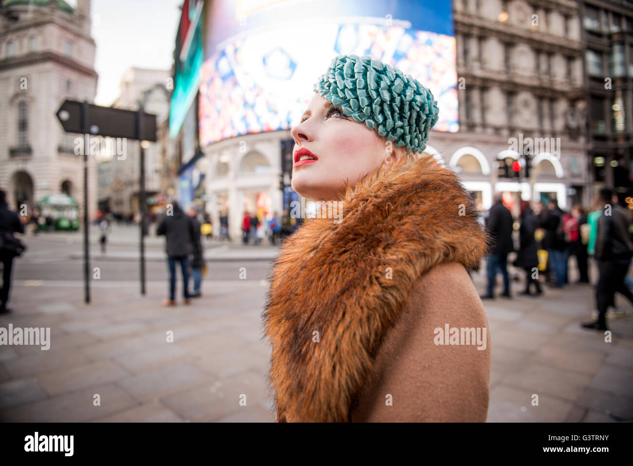 A stylish young woman dressed in 1930s style clothing walking about at Piccadilly Circus. Stock Photo