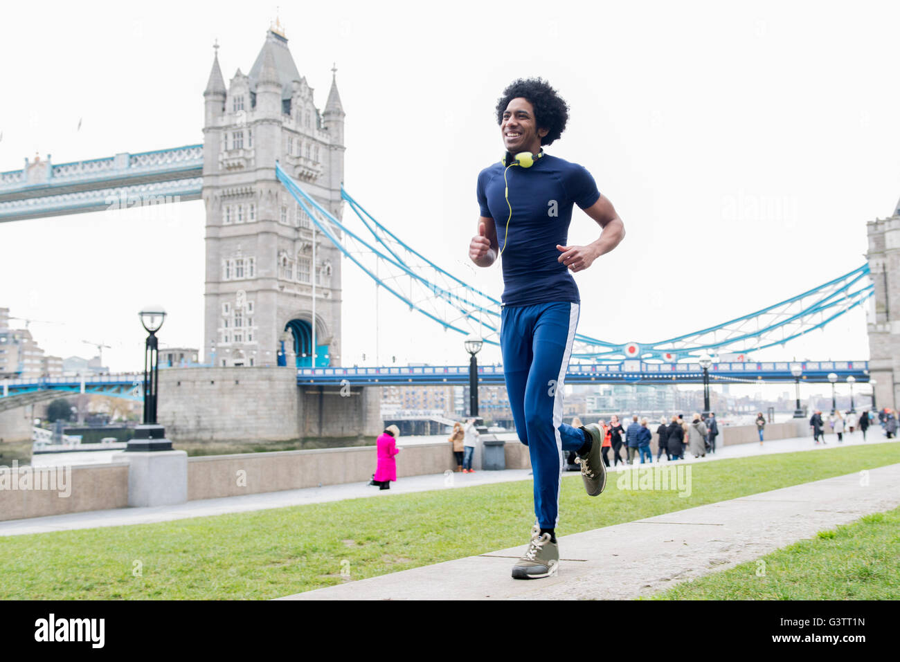 A young man jogging past Tower Bridge in London. - Stock Image
