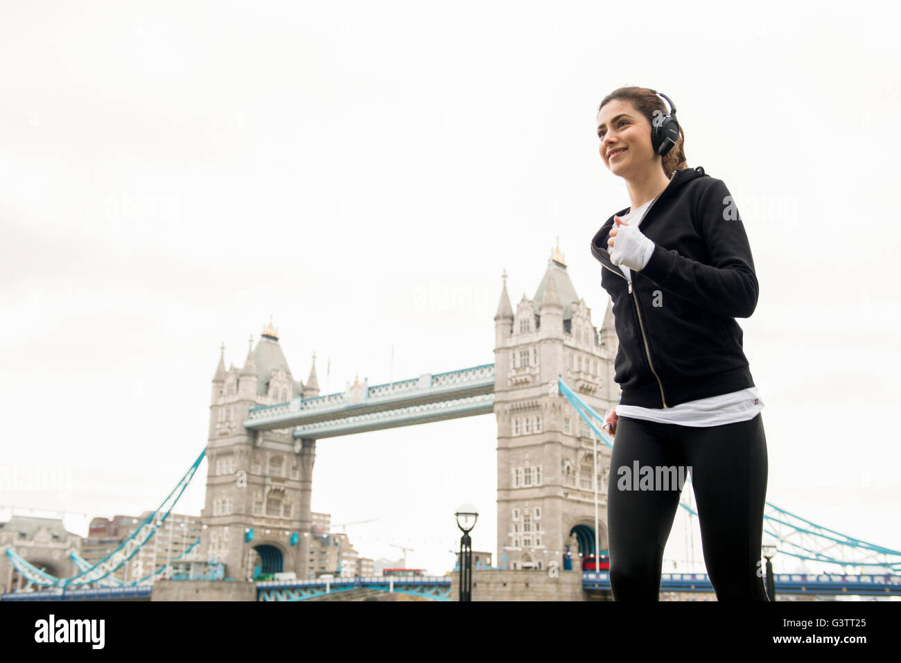 A young woman jogging past Tower Bridge in London. - Stock Image