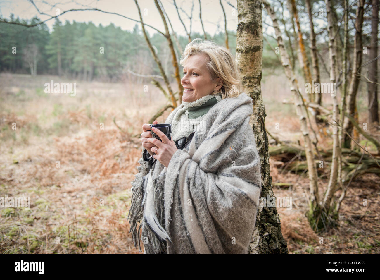 Senior lady standing wrapped in a blanket enjoying a cup of tea. - Stock Image