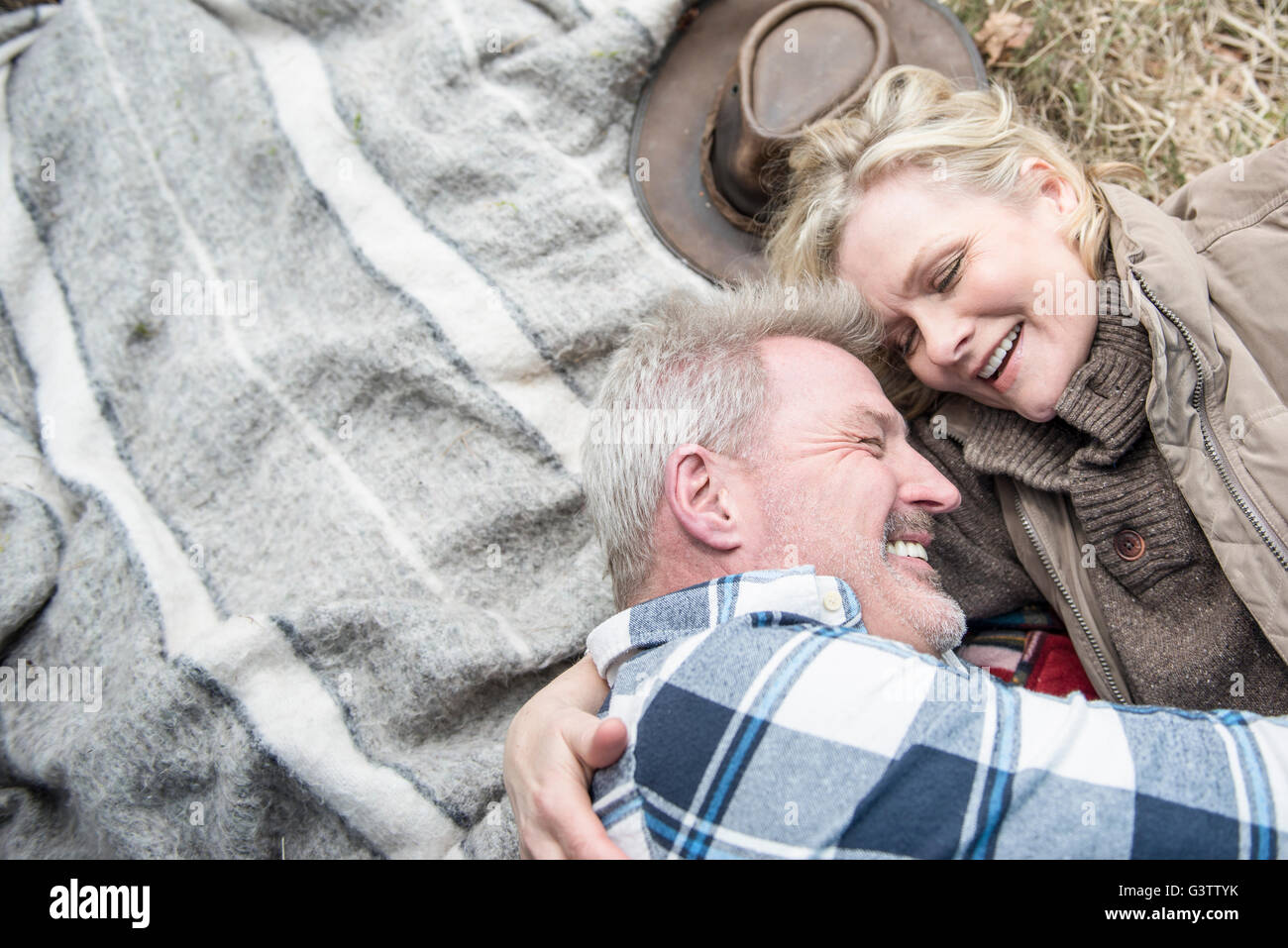 Senior Couple Cuddling Together On A Blanket At Their Campsite