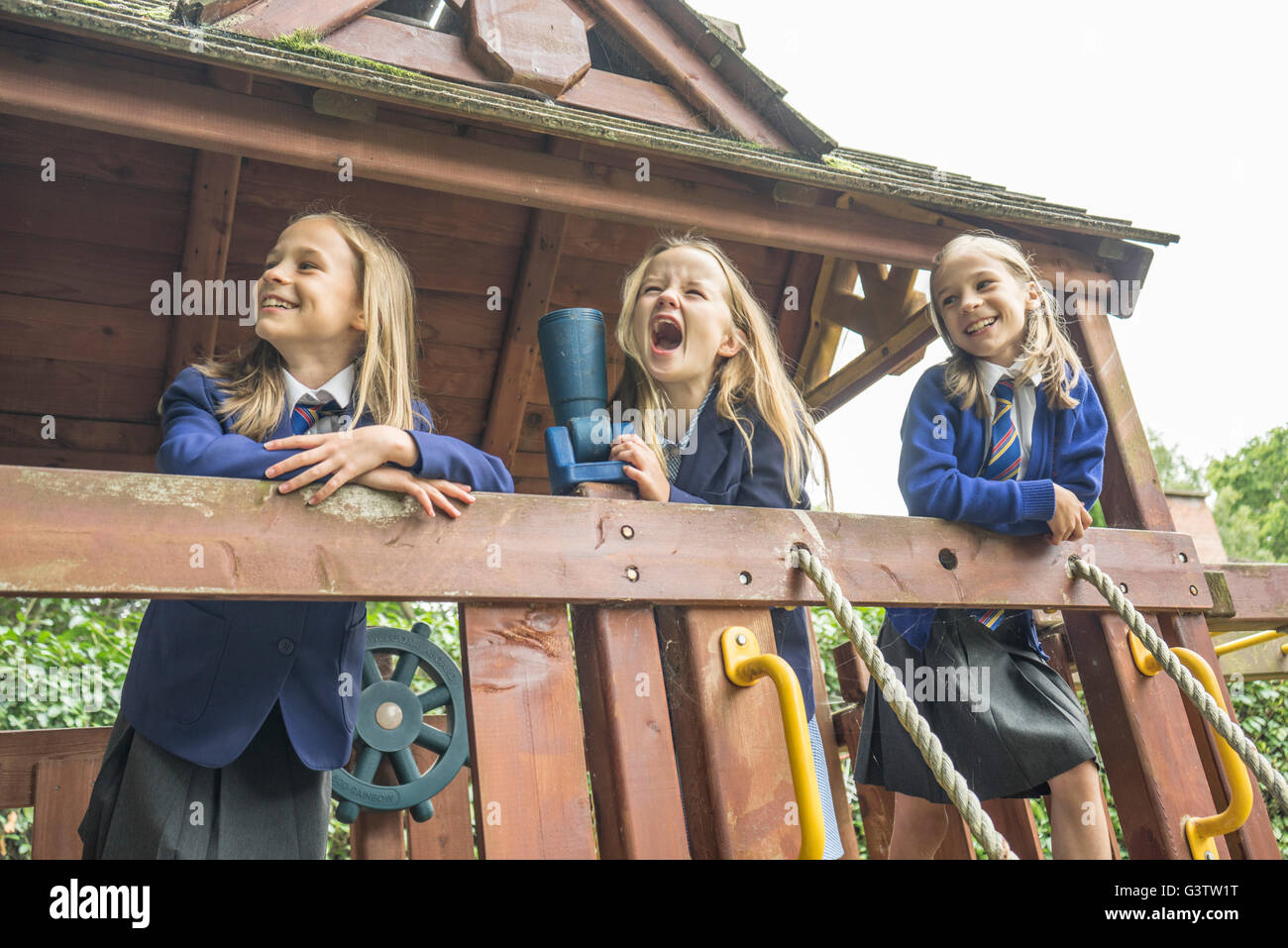 Three girls in school uniform stand together on wooden playground apparatus. - Stock Image
