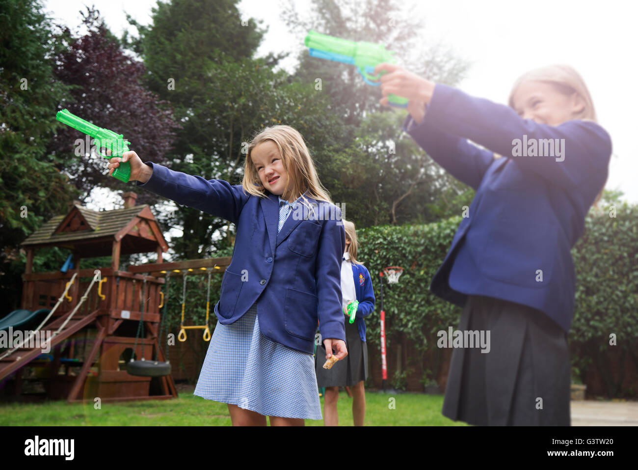 Two ten year old girls in school uniform holding water pistols. - Stock Image
