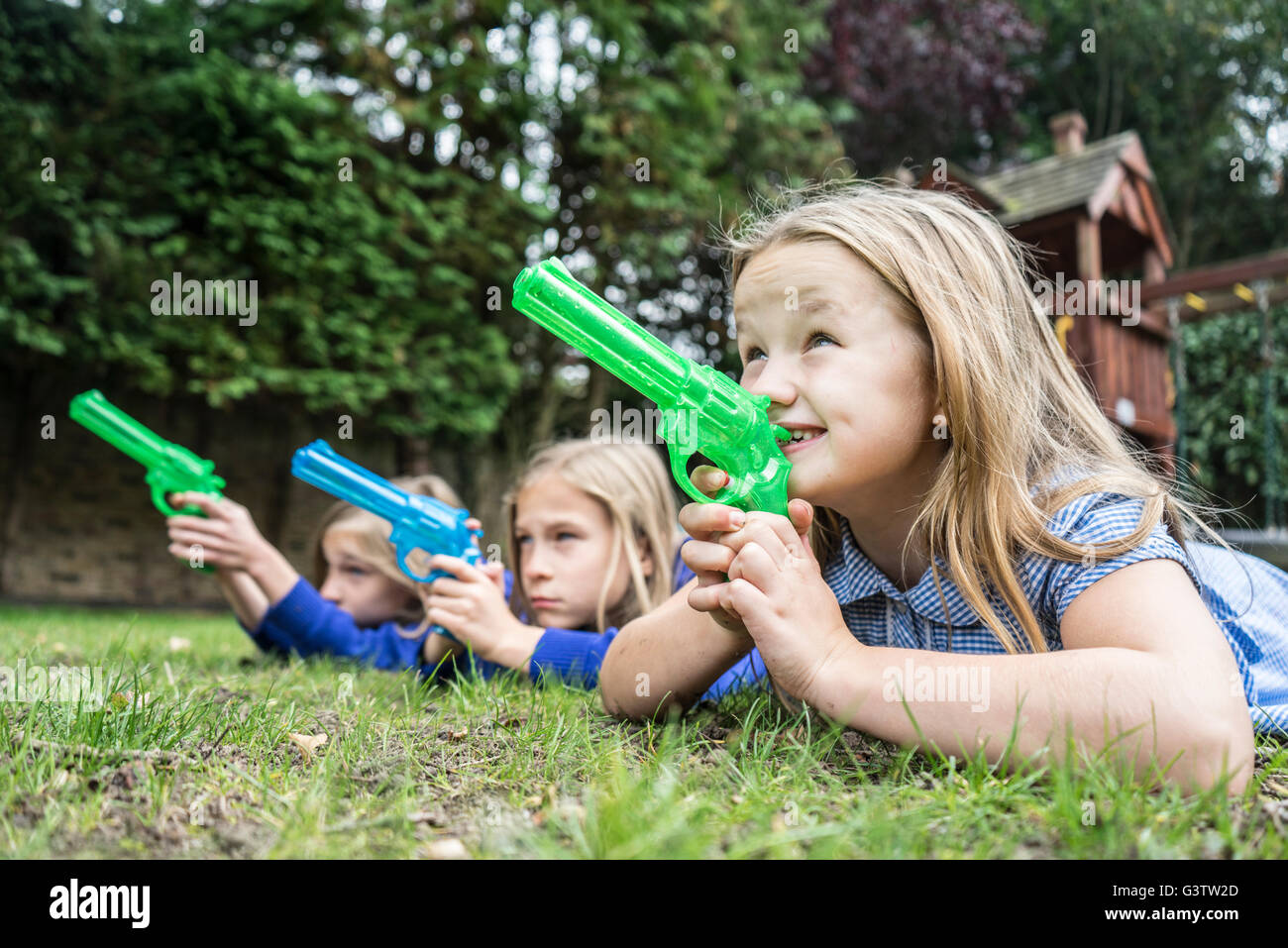 Three ten year old girls in school uniform holding water pistols. - Stock Image