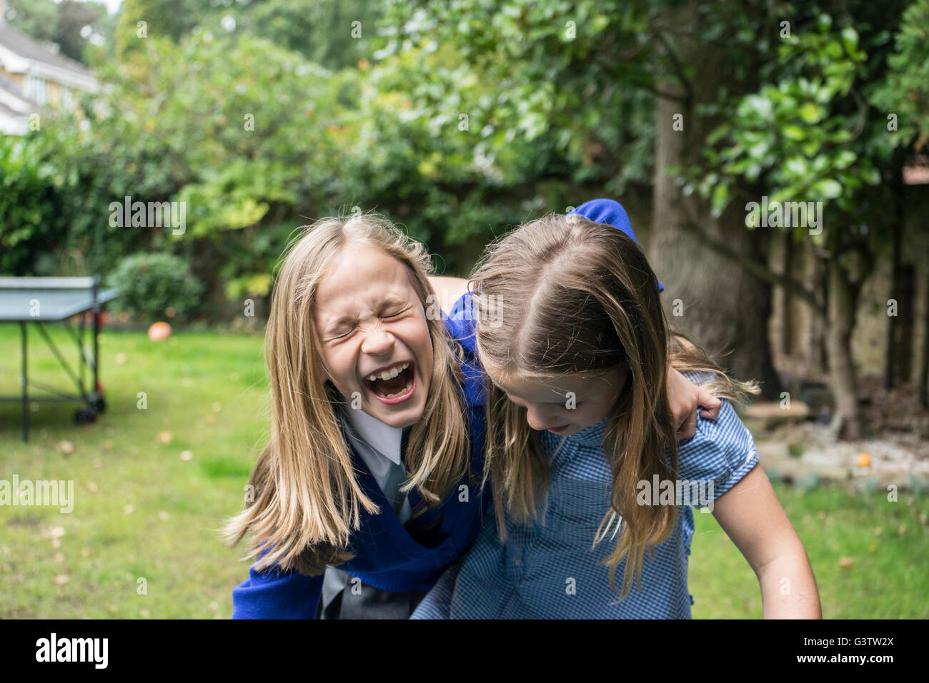 Two ten year old girls in school uniform laughing together outside. - Stock Image