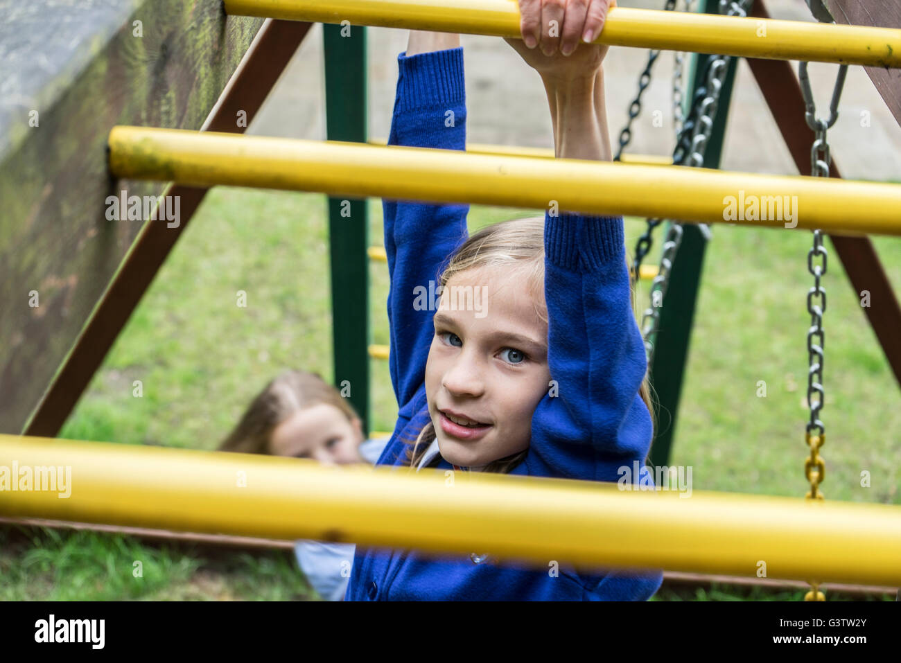 A ten year old girl in school uniform climbing on playground apparatus. - Stock Image