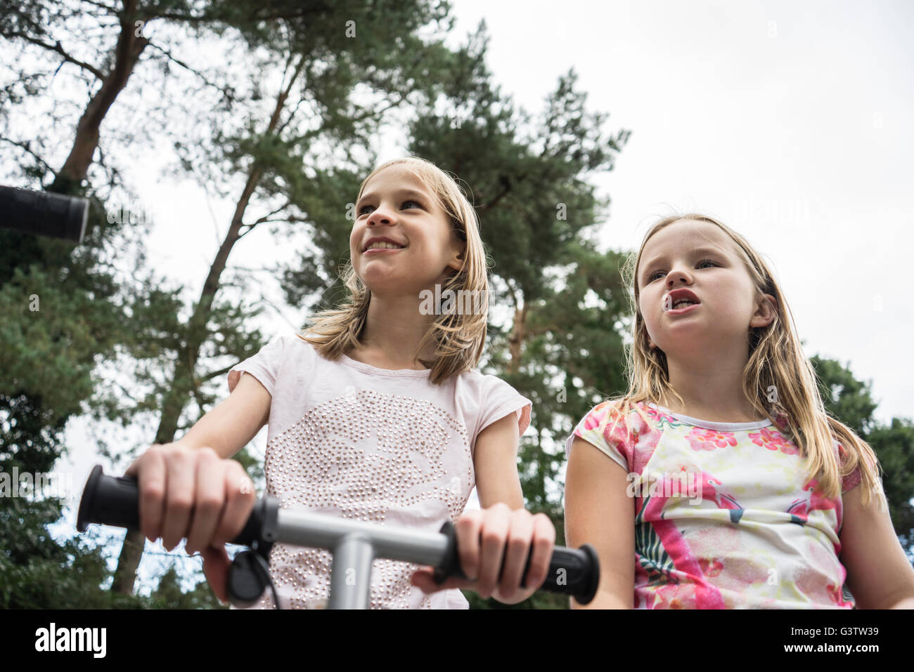Looking up at two ten year old girls playing on a scooter outside. - Stock Image