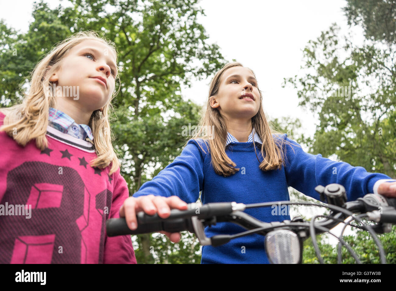 Looking up at two girls playing on a bicycle outside. Stock Photo