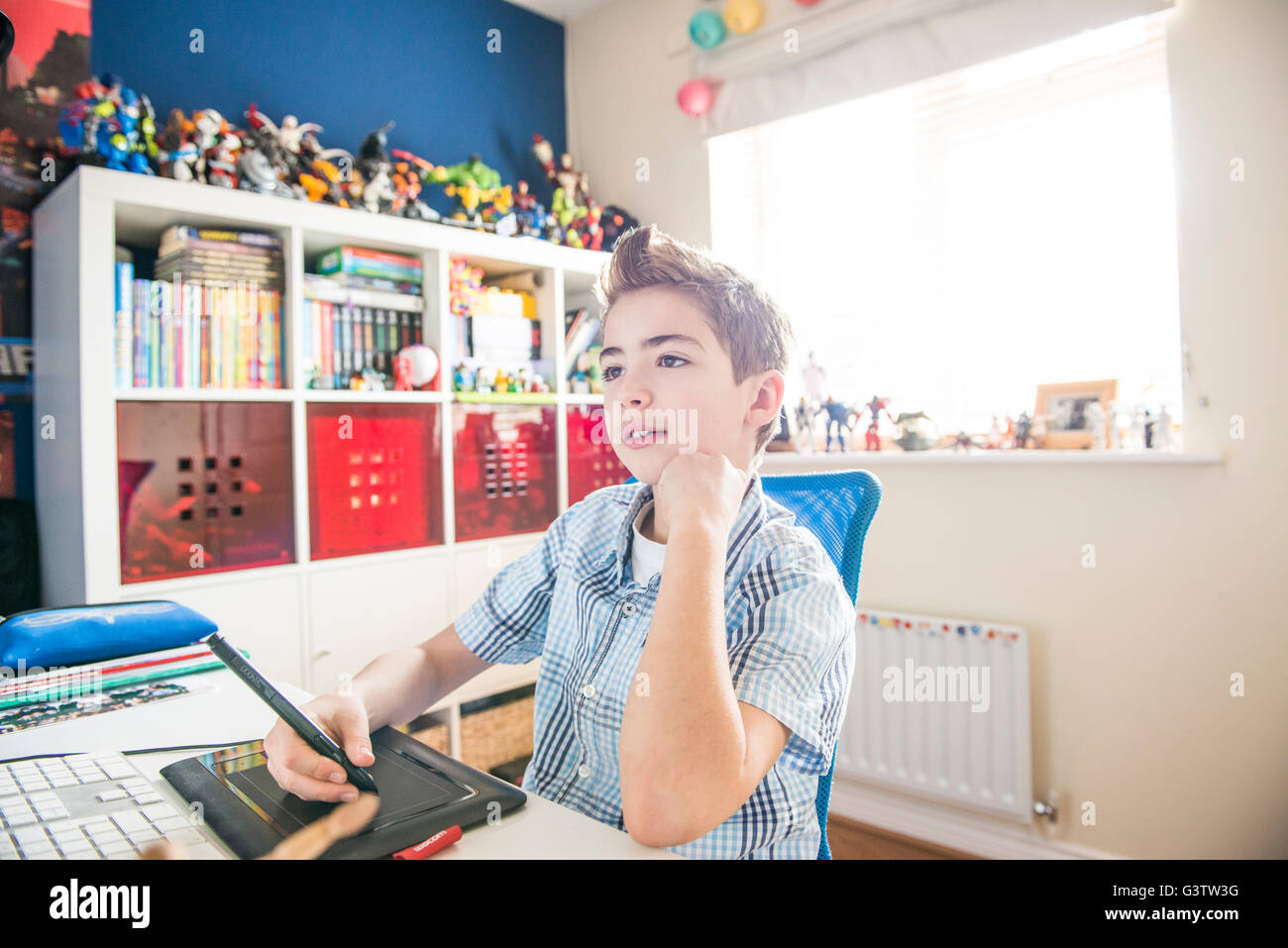 A ten year old boy sitting at a computer in his bedroom. - Stock Image