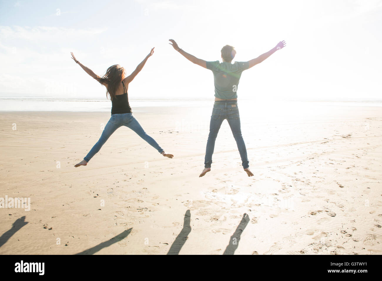 A young couple jumping in the sunshine on the beach at Porthmadog. - Stock Image