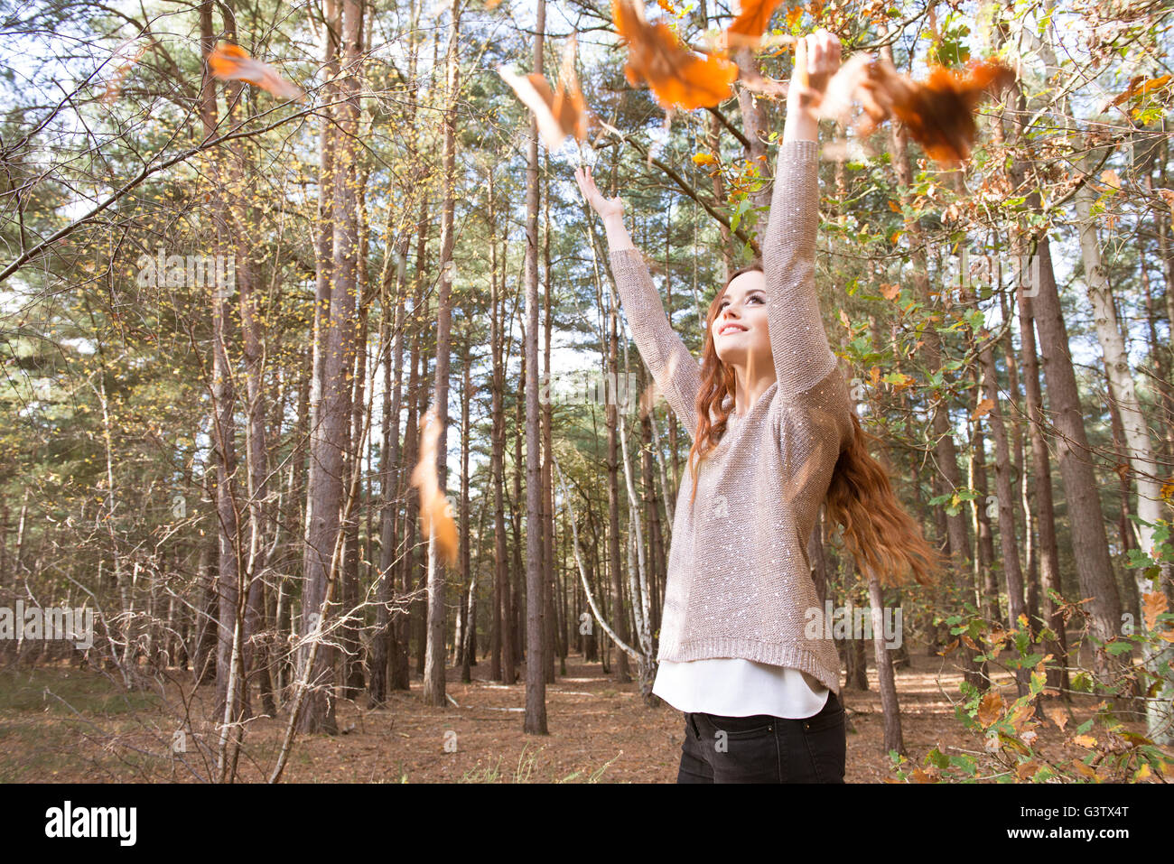 A young woman throwing a handful of leaves in a forest in Autumn. - Stock Image